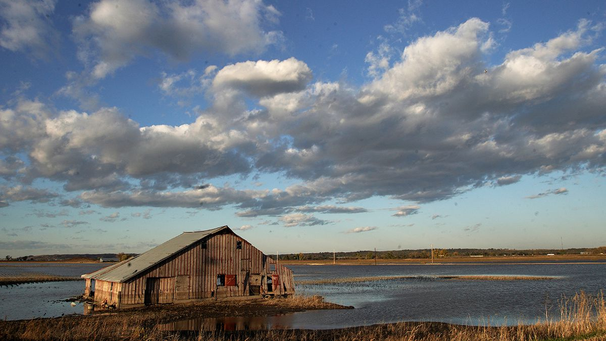 FILE- In this Oct. 22, 2019 photo, a barn sits in floodwaters in Pacific Junction, Iowa. Nebraska, Iowa, Kansas and Missouri are joining forces for a study that will look for ways the states can limit flooding along the Missouri River and give them information about how wetter weather patterns could require changes to the federal government's management of the basin's reservoirs. The states are pooling their money to pay for half of a $400,000 study with the U.S. Army Corps of Engineers to measure how much water flows down the Missouri River. (AP Photo/Nati Harnik)