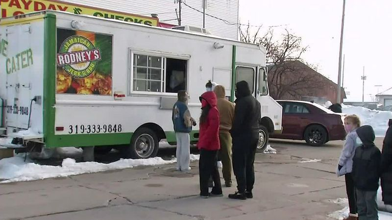 People line up for a free meal at Rodney's Jamaican Jerk & BBQ food truck in Iowa City on...