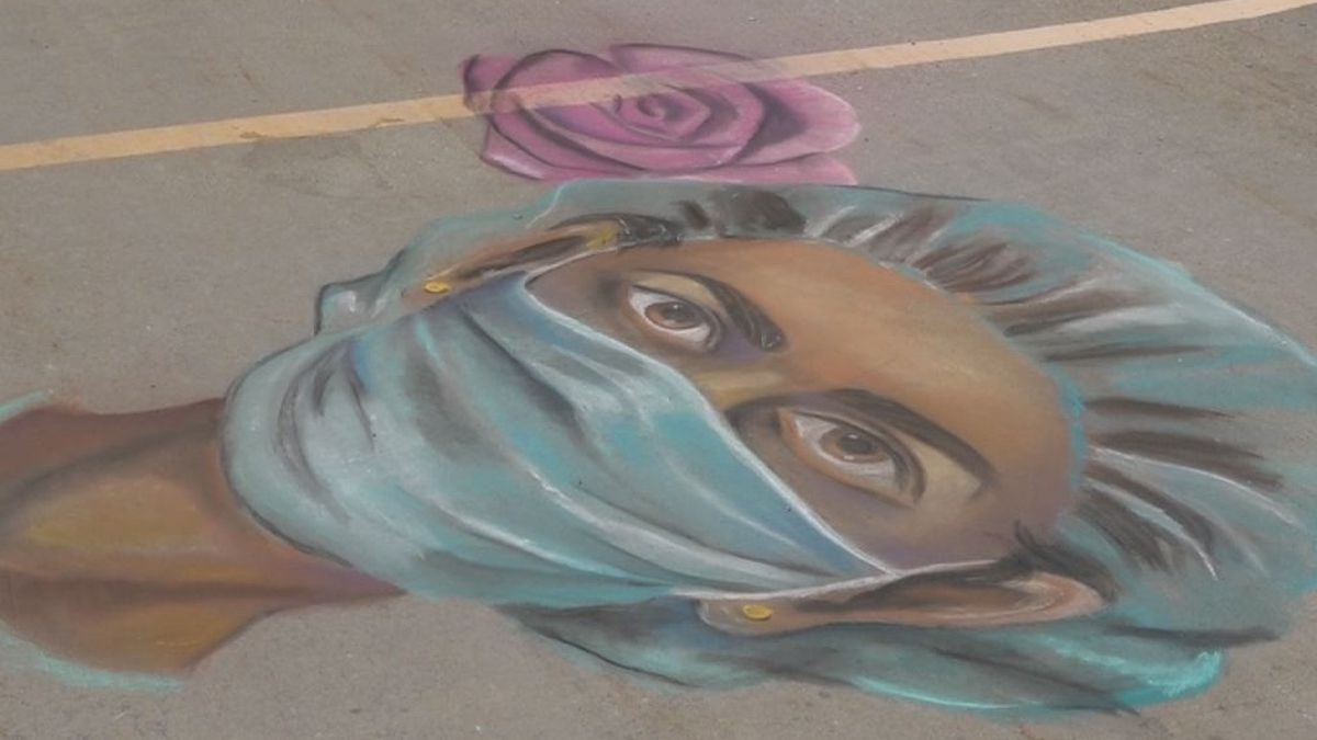 A chalk mural created by two local artists sits outside Mercy Hospital, honoring the healthcare...