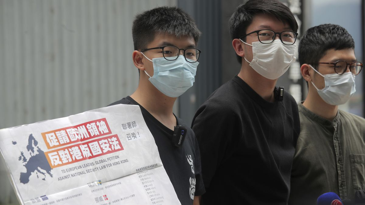 Pro-democracy activists, Joshua Wong, left, Sunny Cheung, center, and Nathan Law holding a placard, speak to media to urge the European leaders against national security law for Hong Kong outside the Legislative Council, in Hong Kong, Wednesday, June 3, 2020. British Prime Minister Boris Johnson says his country stands ready to open the door to close to 3 million Hong Kong citizens if China enacts a national security law for the city. He said in a local newspaper column that the law would curtail freedoms and has many in Hong Kong fearing for their way of life.  (AP Photo/Kin Cheung)
