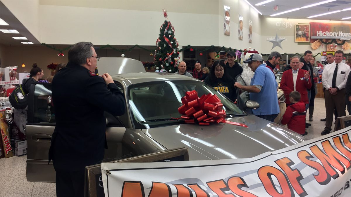 Organizers for the Miles of Smiles event and onlookers stand by a vehicle to be given to a family at the Marion Hy-Vee store on Wednesday, Dec. 4, 2019 (Taylor Holt/KCRG)