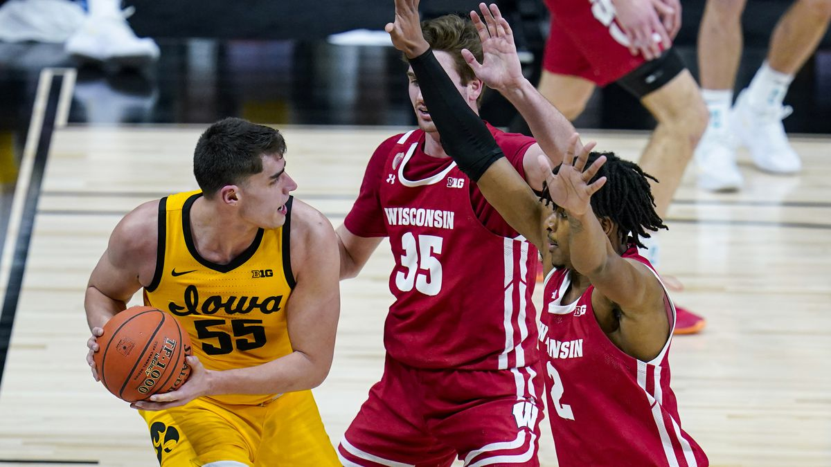 Iowa center Luka Garza (55) gets trapped on the baseline by Wisconsin forwards Nate Reuvers...