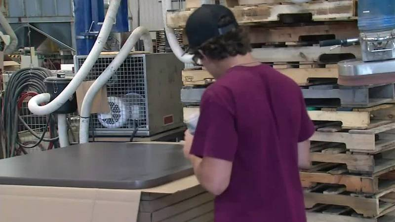 An employee works on a tabletop at Oak Street Manufacturing in Monticello.