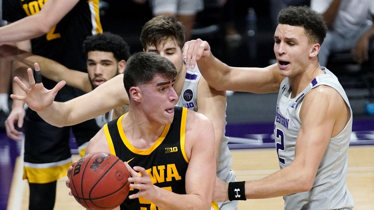 Iowa center Luka Garza (55) looks to pass against Northwestern forward Pete Nance, right, and...