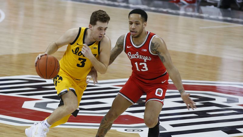 Iowa's Jordan Bohannon, left, brings the ball upcourt against Ohio State's C.J. Walker during...