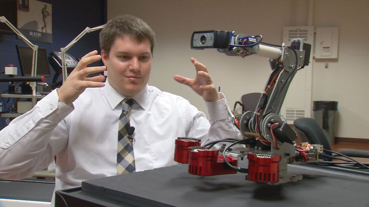 UI Senior Zach Mennen talks about the robot to his right.