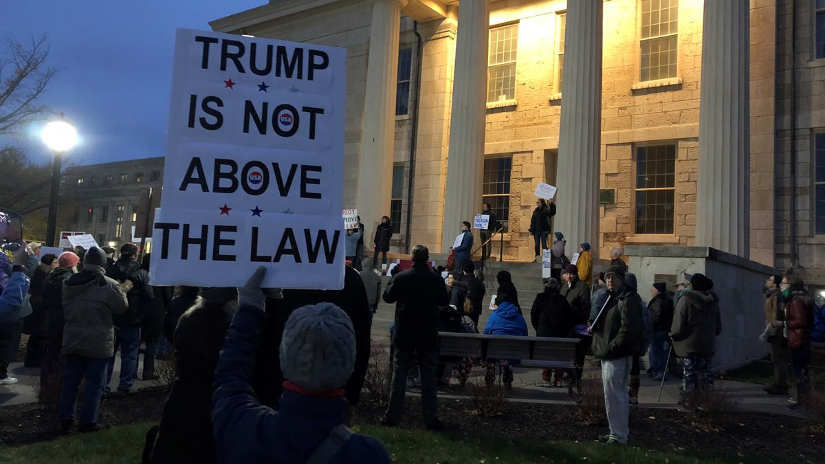 """A group of about 100 in front of the Old Capitol in Iowa City chanted """"hands off..."""