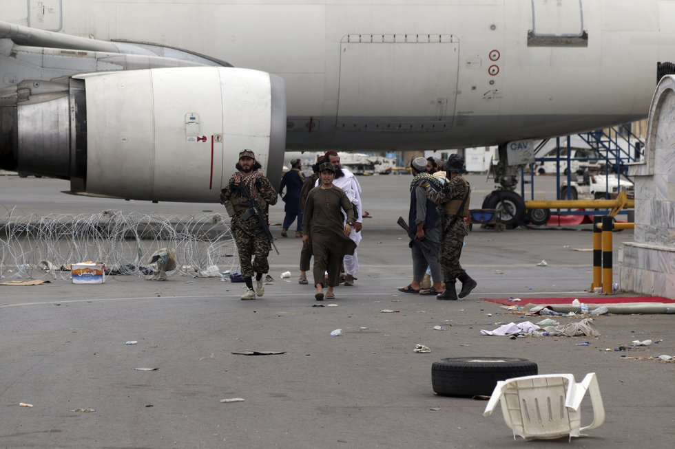 Taliban special force fighters gather inside the Hamid Karzai International Airport after the...