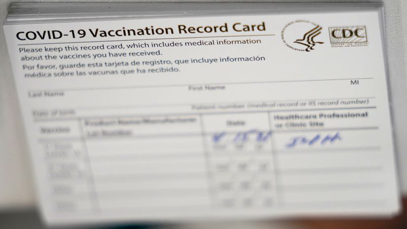 A stack of COVID-19 vaccination record cards are shown at the Christine E. Lynn Rehabilitation...