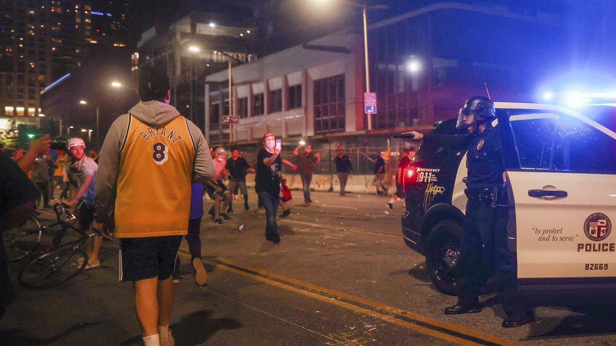 Los Angeles Lakers fans celebrate outside of Staples Center as Los Angeles Police Department officers try to disperse them, Sunday, Oct. 11, 2020, in Los Angeles, after the Lakers defeated the Miami Heat in Game 6 of basketball's NBA Finals to win the championship.