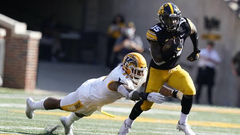 Iowa running back Tyler Goodson (15) runs from Kent State defensive lineman Jabbar Price (41)...