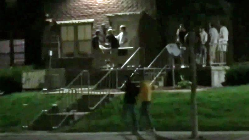 Students hang around the outside entrances to apartments in downtown Iowa City.