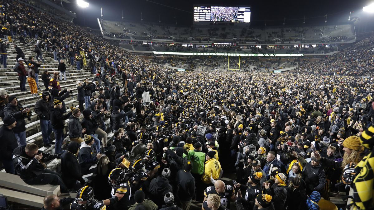 Iowa carries off the Floyd of Rosedale Trophy off the field while surrounded by fans after defeating Minnesota in an NCAA college football game, Saturday, Nov. 16, 2019, in Iowa City, Iowa.