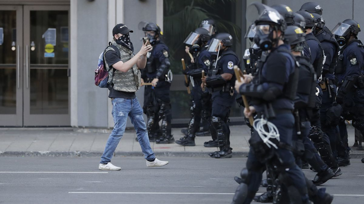 A protester walks with police officers during a protest over the deaths of George Floyd and...