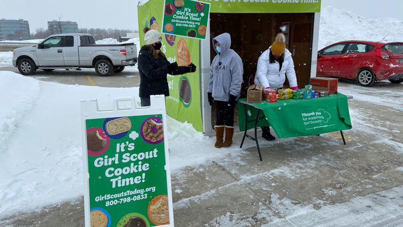Girl Scouts from Troop 5329 sell cookies at a drive-thru booth in Cedar Rapids on Feb. 6, 2021.