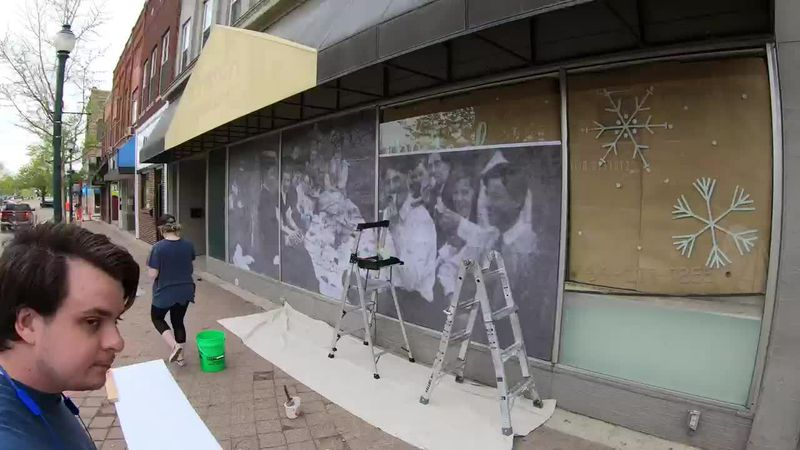 A wheatpaste mural is put up in downtown Cedar Falls in hopes of inspiring togetherness.