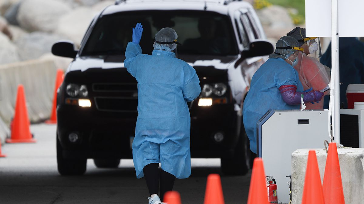 In this Friday, May 1, 2020, photo, a medical worker directs a local resident at a drive-thru COVID-19 testing site in Waterloo, Iowa. (AP Photo/Charlie Neibergall)