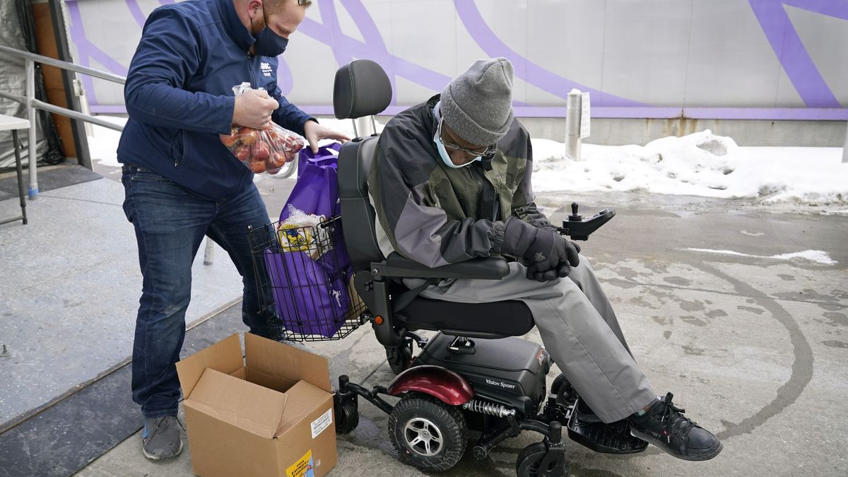 Des Moines Area Religious Council operations manager Joe Dolack, left, loads a Farmers to...