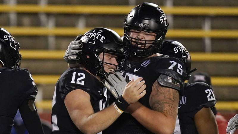 Iowa State quarterback Hunter Dekkers (12) celebrates with teammate Sean Foster (75) after...