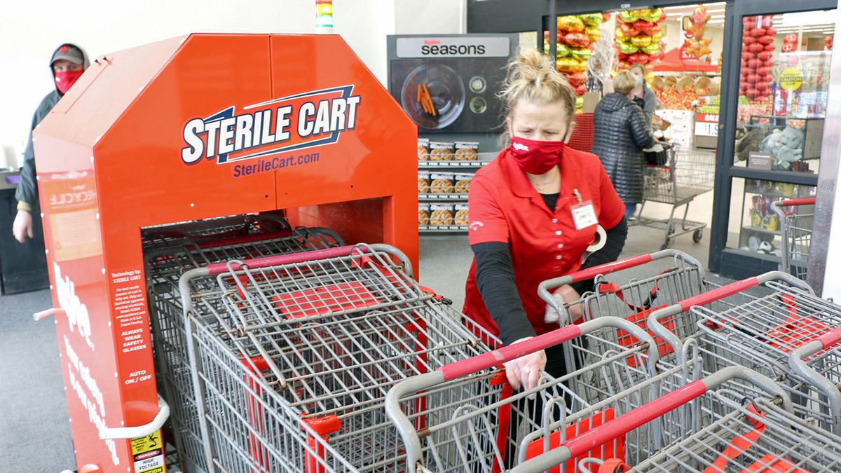A Hy-Vee employee manages a cart sterilization machine in a photo provided by the company.
