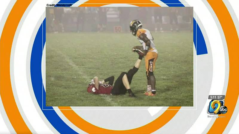 A picture of an Iowa high school football player helping a rival has spread across the internet.