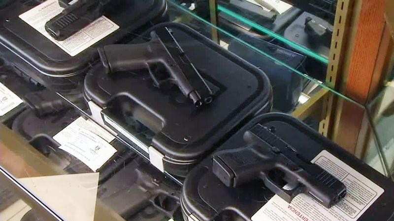 Guns are on display in a case at Cedar Valley Outfitters on Tuesday, Mar. 2, 2021. A...