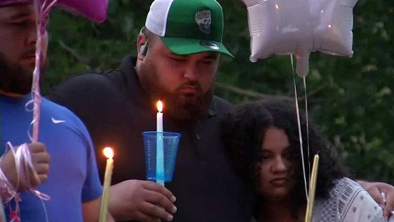 People gather in Cedar Rapids at a vigil for Tyliyah L. Whitis, of Peoria, Ill., on Wednesday,...
