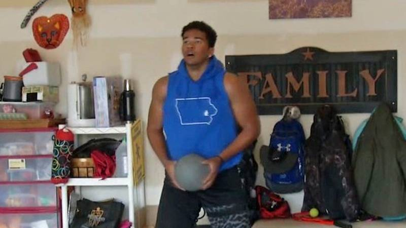 T.J. Bollers, a star football player for Clear Creek-Amana High School, works out in the garage...
