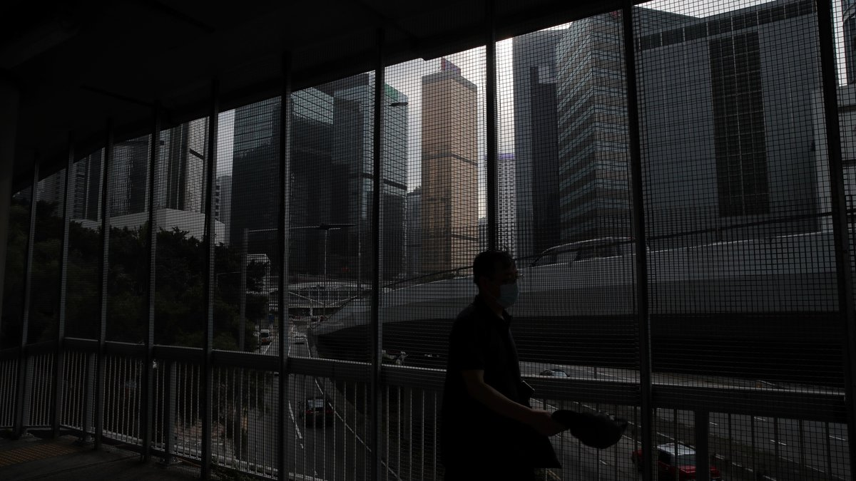 A man walks on a bridge which is covered by fence to protect from protesters in Hong Kong,...