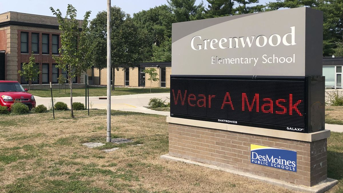 A sign outside of Greenwood Elementary School promotes mask-wearing on Thursday, Sept. 17, 2020, in Des Moines, Iowa. A dispute between Iowa's governor and the state's largest school district could mean summer school for students and crippling bills for the school system. Des Moines school officials have repeatedly refused to abide by Republican Gov. Kim Reynolds' order that districts hold at least half their classes in-person, saying it's not safe.