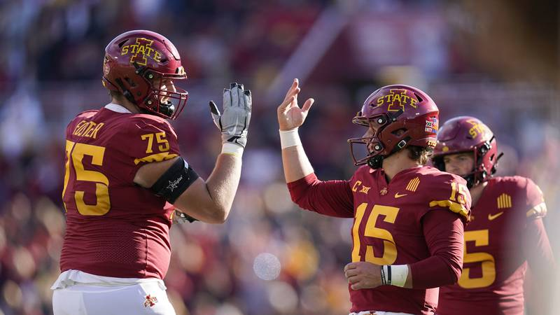 Iowa State quarterback Brock Purdy (15) celebrates with teammate Sean Foster (75) after...