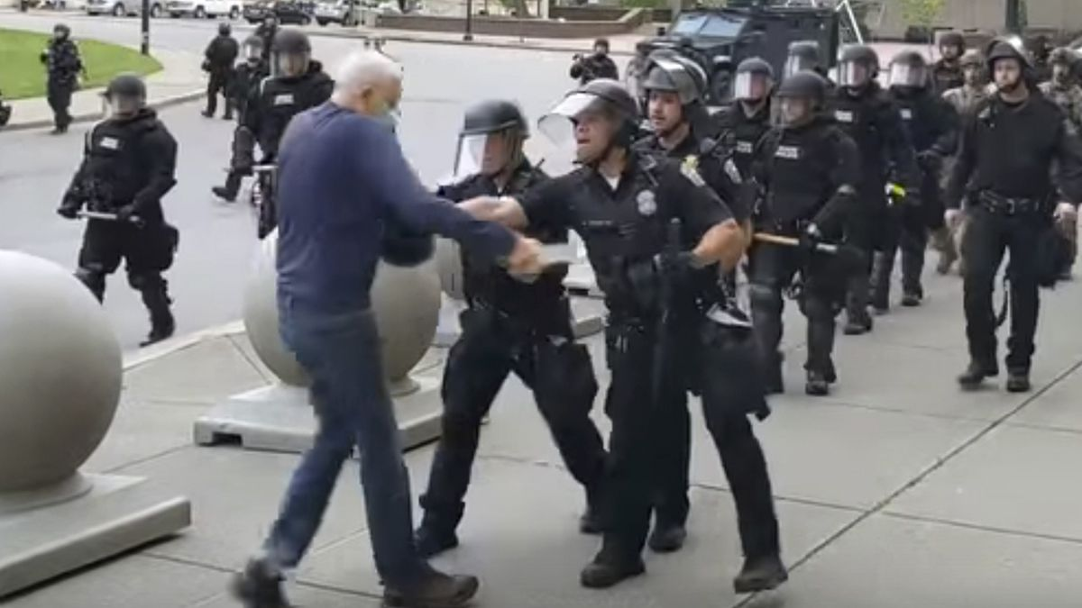 """In this image from video provided by WBFO, a Buffalo police officer appears to shove a man who walked up to police Thursday, June 4, 2020, in Buffalo, N.Y. Video from WBFO shows the man appearing to hit his head on the pavement, with blood leaking out as officers walk past to clear Niagara Square. Buffalo police initially said in a statement that a person """"was injured when he tripped & fell,"""" WIVB-TV reported, but Capt. Jeff Rinaldo later told the TV station that an internal affairs investigation was opened. Police Commissioner Byron Lockwood suspended two officers late Thursday, the mayor's statement said."""