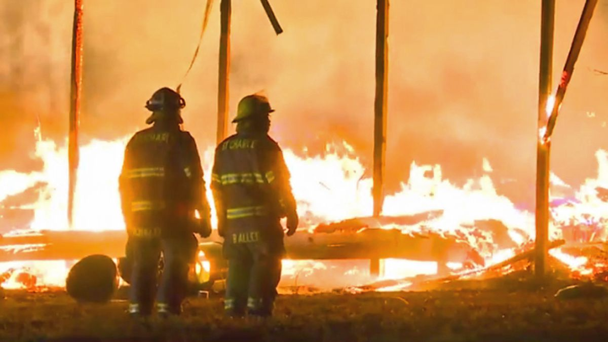 Firefighters look on as an intense fire consumes a Clive Fire Department lieutenant's home on Saturday, Nov. 30, 2019 (KCCI)