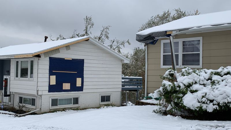 Snow blankets Chris Stumpff's roof, right, in southwest Cedar Rapids, along with the tarp...