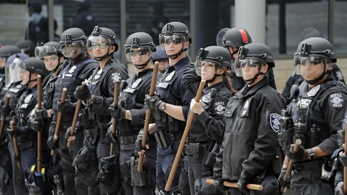 A line of police officers surrounding City Hall on Wednesday, June 3, 2020, in Seattle, look towards demonstrators following protests over the death of George Floyd, an African American who died on May 25 after a white Minneapolis police officer pressed a knee into his neck for several minutes even after he stopped moving and pleading for air.  (AP Photo/Elaine Thompson)