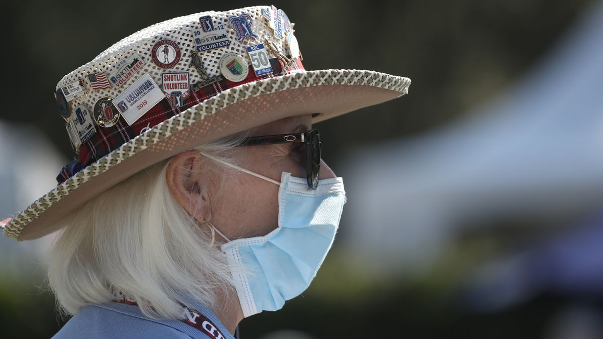 Cheryl Bearce, a volunteer working the first tee, wears a mask as a precaution against the coronavirus, at the start the third round of the RBC Heritage golf tournament, Saturday, June 20, 2020, in Hilton Head Island, S.C.