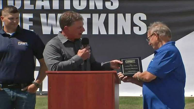 Charles Watkins accepts a plaque honoring his 4 million safe driving miles as a trucker for...
