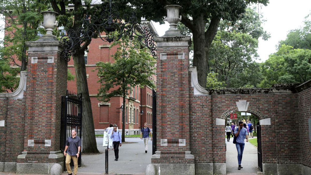 FILE - In this Aug. 13, 2019, file photo, pedestrians walk through the gates of Harvard Yard at Harvard University in Cambridge, Mass. Harvard and the Massachusetts Institute of Technology filed a federal lawsuit Wednesday, July 8, 2020, challenging the Trump administration's decision to bar international students from staying in the U.S. if they take classes entirely online this fall. Some institutions, including Harvard, have announced that all instruction will be offered remotely in the fall during the ongoing coronavirus pandemic. (Source: AP Photo/Charles Krupa, File)