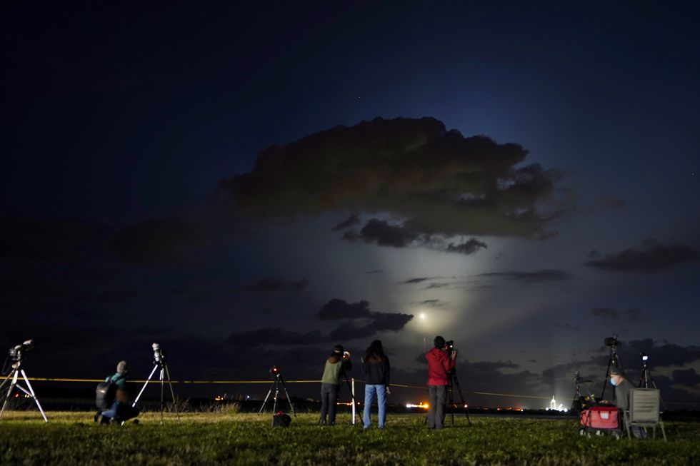 Photographers watch SpaceX Falcon 9 rocket with the Crew Dragon space capsule lift off from pad...