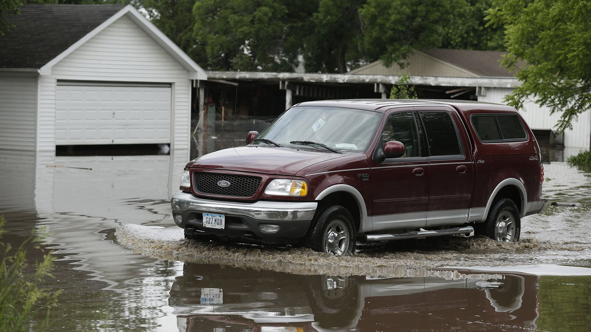 A resident drives through flood waters in front of a garage, Tuesday, June 25, 2013, in New...