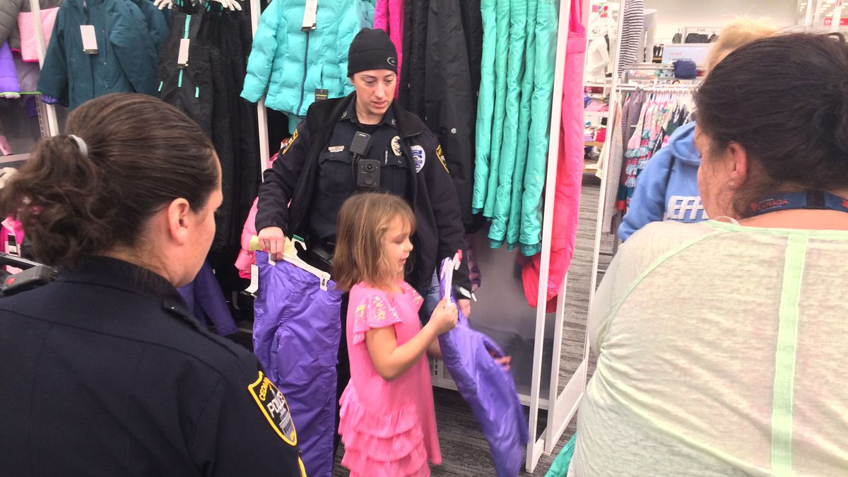 Officers help a family pick out winter clothing for children.  This was the 17th Santa Cop event for Cedar Rapids.