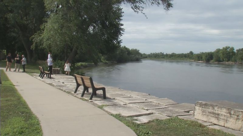 People at Celebration Park looking at the Cedar River in Vinton.