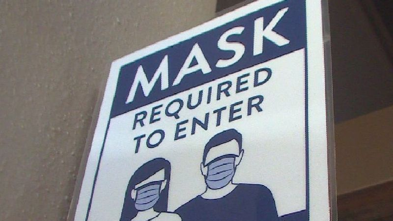 A sign hangs on the window of a Colorado store that states masks are required to enter.