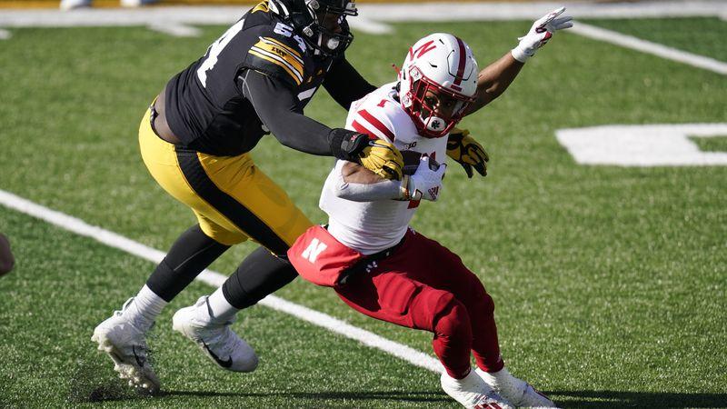 Iowa defensive tackle Daviyon Nixon, left, tackles Nebraska wide receiver Wan'Dale Robinson...