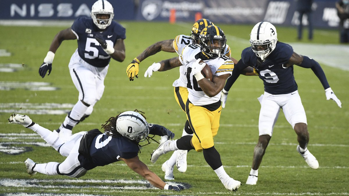 Iowa running back Mekhi Sargent (10) breaks a tackle attempt by Penn State safety Jonathan...