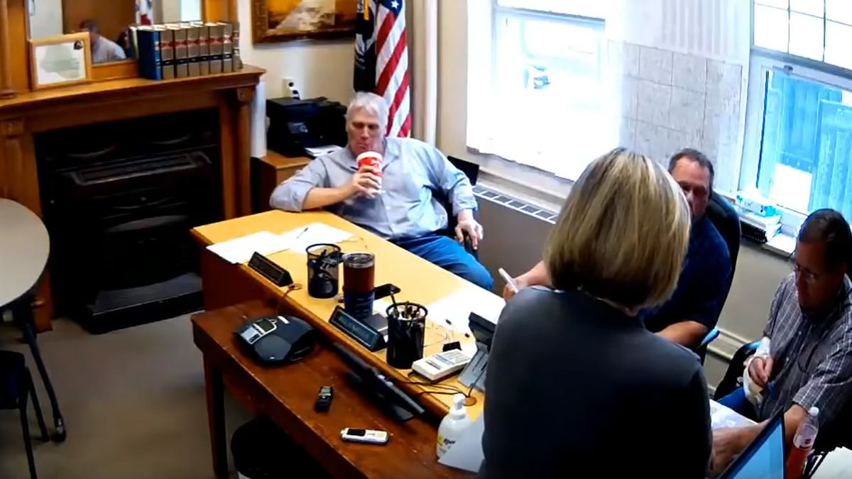 Winnebago County Supervisor Mike Stensrud, left, takes a drink from a cup that police said contained alcohol during a board meeting on May 21, 2019 (Winnebago County/YouTube)