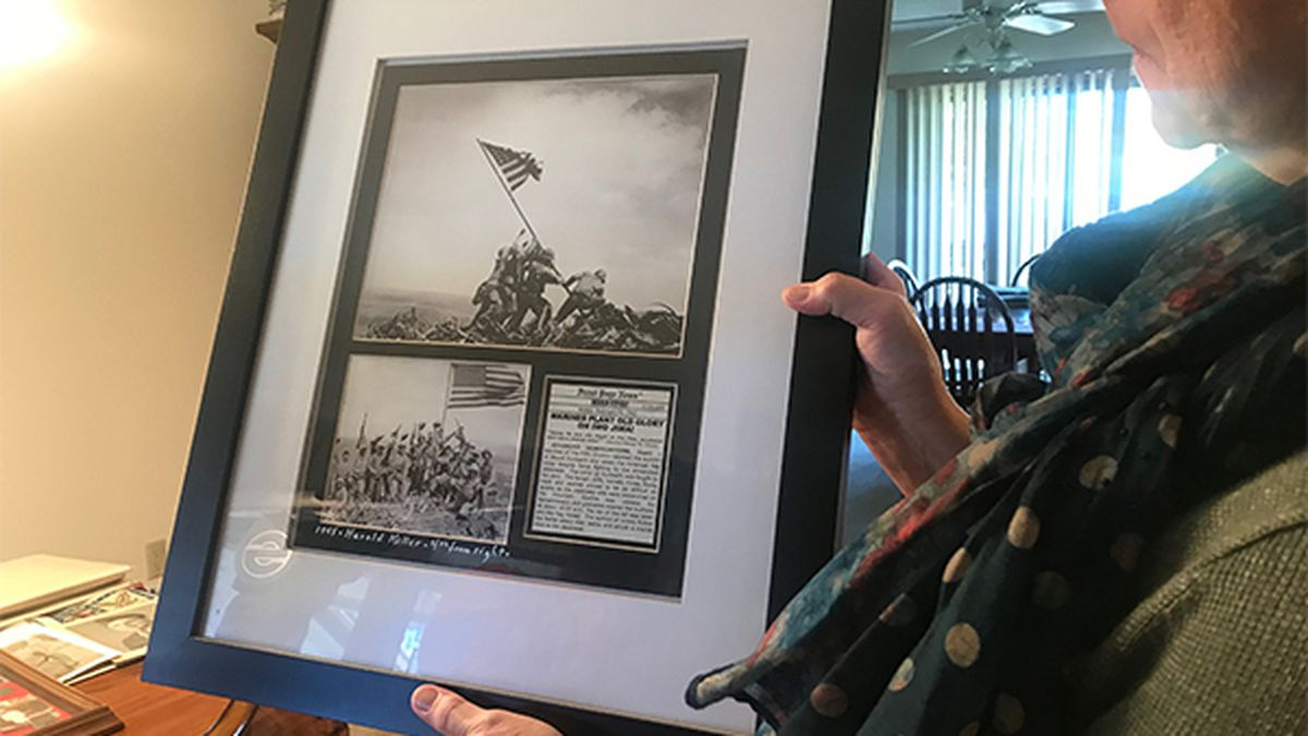 Kay Maurer, of Clarence, holds up one of the most renowned photos in military history - the six men raising the American flag at Iwo Jima during World War 2. Associated Press photographer Joe Rosenthal took the iconic photo on top of Mount Suribachi during a battle between American and Japanese forces in 1945. Now more than 70 years later, the US Marine Corps says one man in the picture, Corporal Harold P. Keller, is actually from Brooklyn, Iowa. (TAYLOR HOLT/KCRG)
