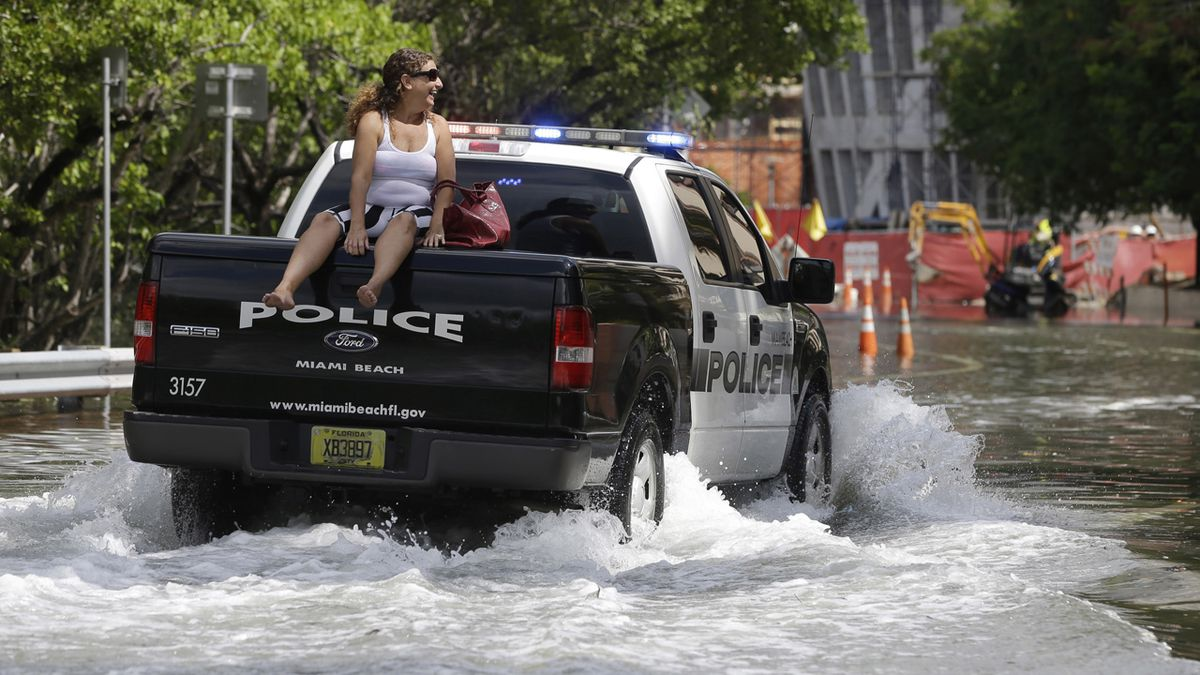 FILE- In this Sept. 30, 2015 file photo, a woman gets a ride on a police truck navigating a flooded street in Miami Beach, Fla. The street flooding was in part caused by high tides due to the lunar cycle, according to the National Weather Service.