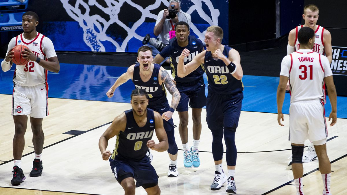 Oral Roberts players celebrate after beating Ohio State in a first-round game in the NCAA men's...