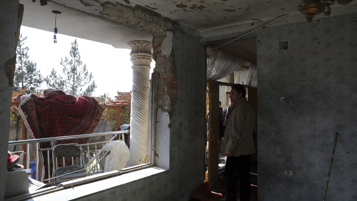 Afghans inspect a damaged house after a mortar shell attack in Kabul, Afghanistan, Saturday,...